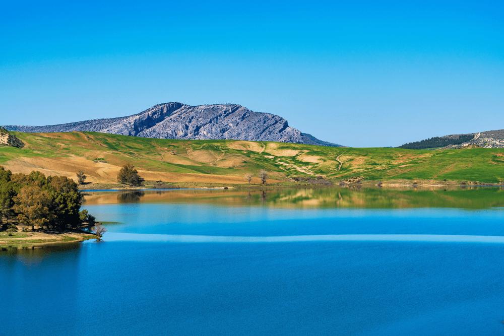 Bei Málaga erstreckt sich eine idyllische, riesige Landschaft aus klaren Stauseen, die sich in eine bergige Felslandschaft mit grünen Nadelwäldern schmiegen.