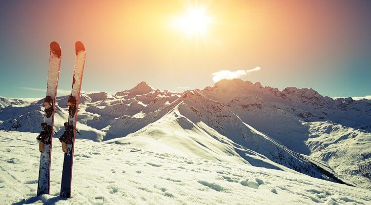 Skibretter stecken im Schnee und im Hintergrund sieht man die schneebedeckten Berge mit untergehender Sonne