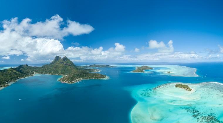 Blick aus dem Helikopter auf die Inselkette Französisch-Polynesien und das türkisblaue Wasser des Südpazifiks