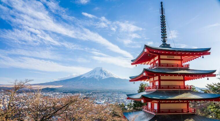 Traditionell japanisches Gebäude im Vordergrund und im Hintergrund der Vulkan Fuji