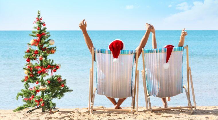 Zwei Menschen sitzen mit Nikolausmützen am Strand neben einem Weihnachtsbaum