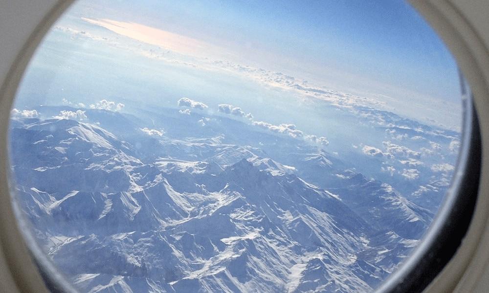 Bild aus dem Flugzeugfenster mit Blick auf die Alpen.