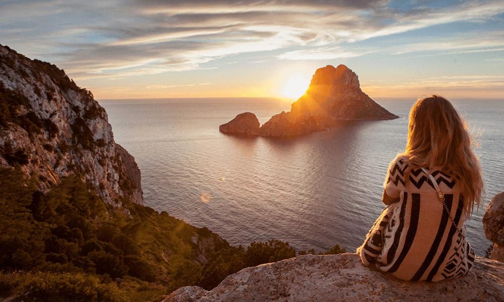 Frau schaut sich den Sonnenuntergang auf Ibiza an.