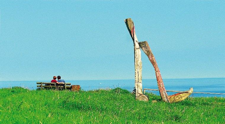 Ein Paar sitzend auf einer Bank mit Blick aufs Meer
