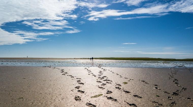 Wattenmeer mit Fussabdrücken blauer Himmel