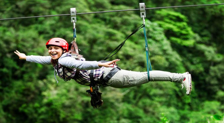 Frau beim Ziplining über den Baumkronen